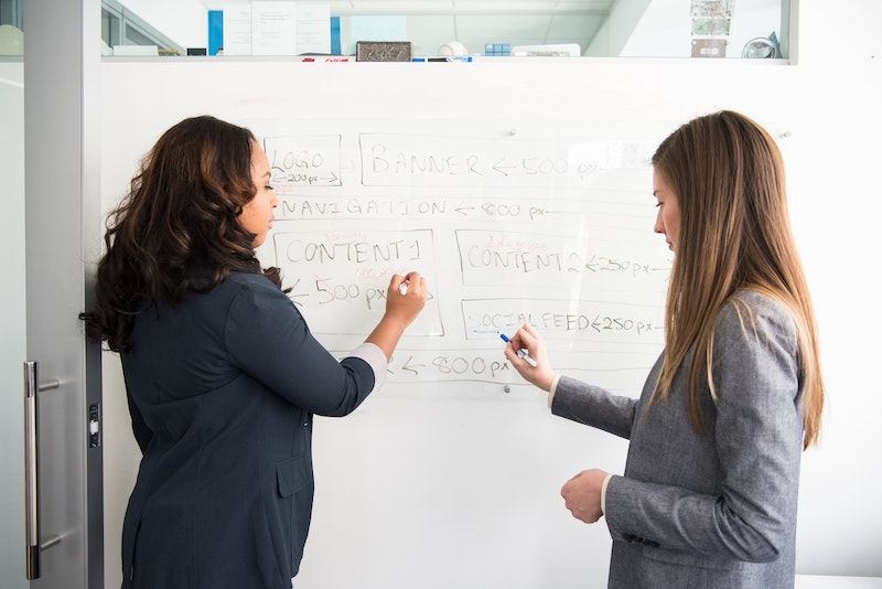 two content developers standing in front of the board