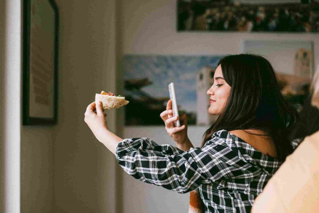 micro influencer woman taking picture of food